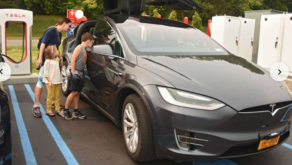 A family checks out an electric or plug-in Tesla that is being recharged.