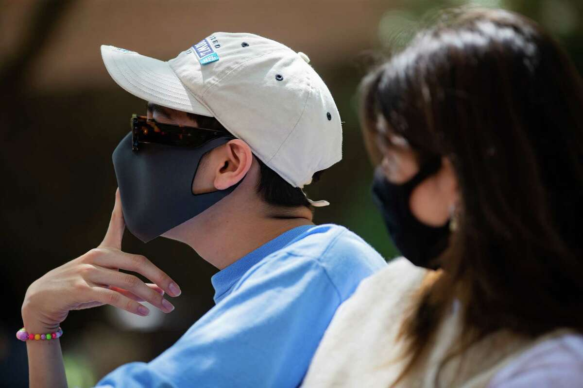Rice University student Miguel Luna, 21, wears a protective mask at campus because of his proximity to Maya Chamberlain, 20, Monday, April 26, 2021, in Houston. Rice University will no longer require people to wear a mask outdoors if they are at least three feet apart.