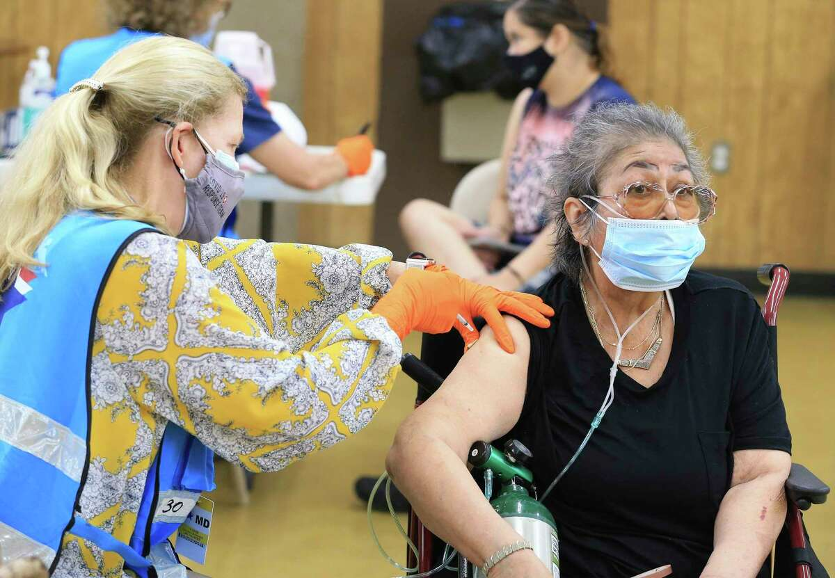 Mary Ruppel, right, receives a COVID-19 vaccine at a pop-up clinic on San Antonio's Southwest Side at the St. Vincent de Paul Columbus Club at 5763 Ray Ellison Drive on April 26, 2021. A slow but steady flow of people appeared to get the Pfizer vaccinations.