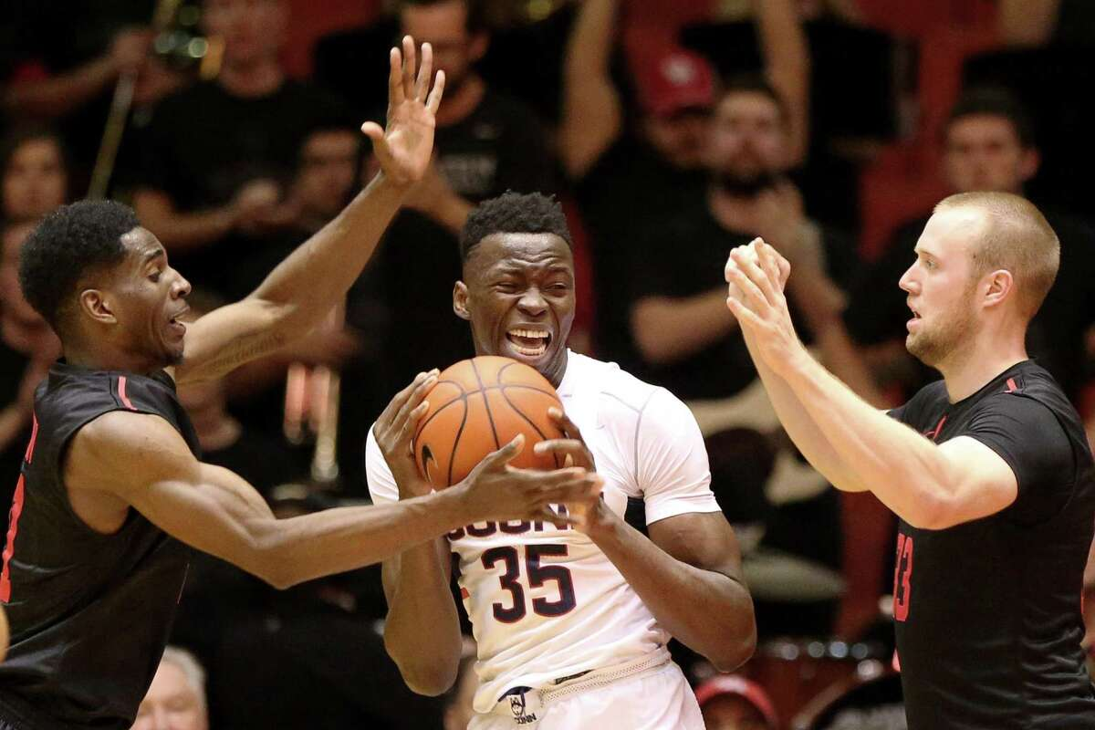 UConn center Amida Brimah (35) is guarded by Houston's Damyean Dotson, left, and Kyle Meyer under the basket during a 2017 game.