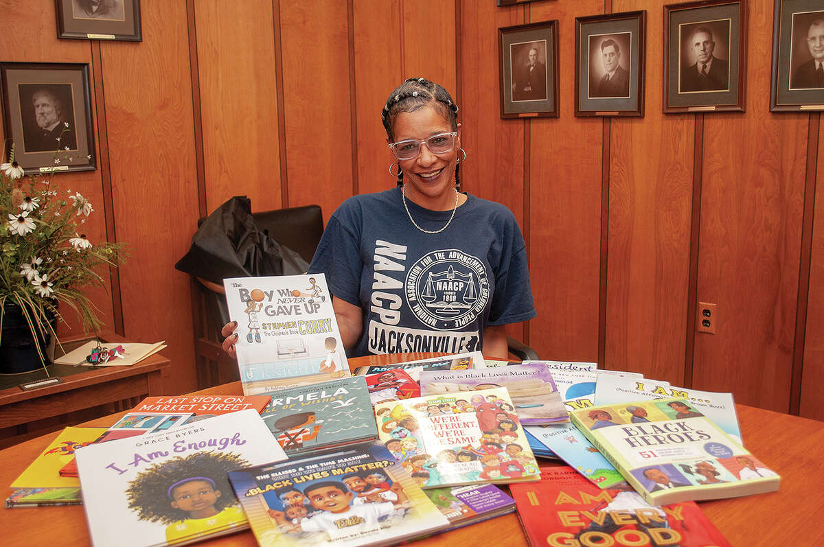 Regina Williams, youth adviser president for Jacksonville's NAACP chapter, holds one of the books that will be available at all Jacksonville elementary schools and Jacksonville Middle School for students to learn about other cultures. Funding for the books came from a grant awarded by Prairieland United Way.
