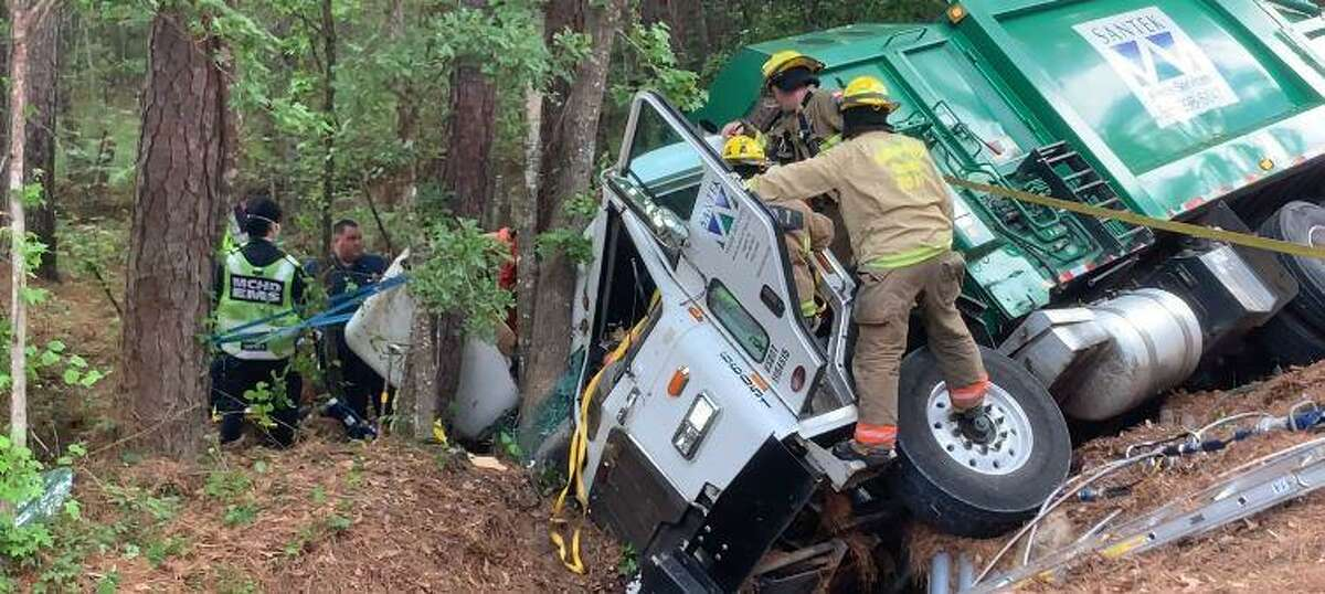 First responders on Monday morning work to free a man entrapped in a dumpster truck on Old Highway 105 at Metts Road in north Montgomery County.