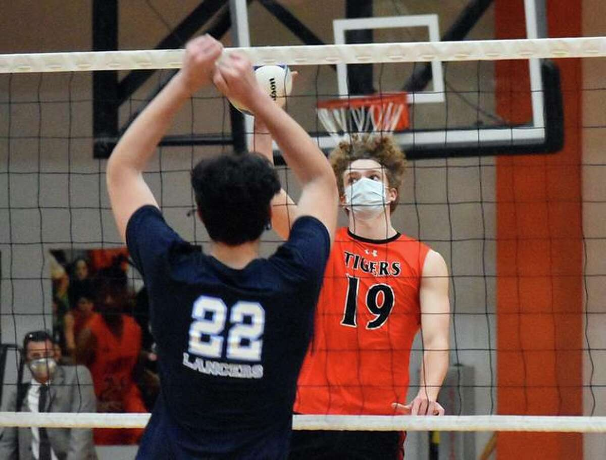 Edwardsville's Evan Reid attempts to tip a ball over the net against Belleville East on Monday in Edwardsville.