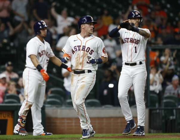 Houston Astros Carlos Correa (1) and Myles Straw (3) celebrate their runs scored on Jose Altuve's RBI single during the fourth inning of an MLB baseball game at Minute Maid Park, Monday, April 26, 2021, in Houston. Photo: Karen Warren/Staff Photographer / @2021 Houston Chronicle