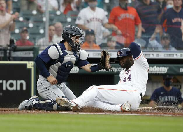 Houston Astros Yordan Alvarez (44) slides home to score a run against Seattle Mariners catcher Luis Torrens (22) on Yuli Gurriel's RBI single during the first inning of an MLB baseball game at Minute Maid Park, Monday, April 26, 2021, in Houston. Photo: Karen Warren/Staff Photographer / @2021 Houston Chronicle