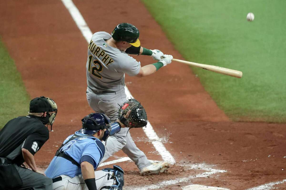 ST. PETERSBURG, FL - APRIL 26: Sean Murphy #12 of the Oakland Athletics hits a two-run home run in front of Mike Zunino #10 of the Tampa Bay Rays and umpire Sean Barber #29 in the fourth inning of a game at Tropicana Field on April 26, 2021 in St. Petersburg, Florida. (Photo by Mike Carlson/Getty Images)