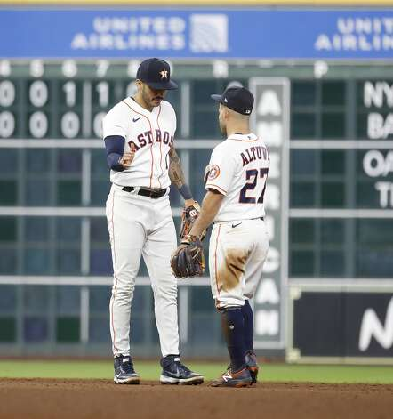 Houston Astros shortstop Carlos Correa (1) and Jose Altuve (27) celebrate the Astros 5-2 win over the Seattle Mariners after an MLB baseball game at Minute Maid Park, Monday, April 26, 2021, in Houston. Photo: Karen Warren/Staff Photographer / @2021 Houston Chronicle