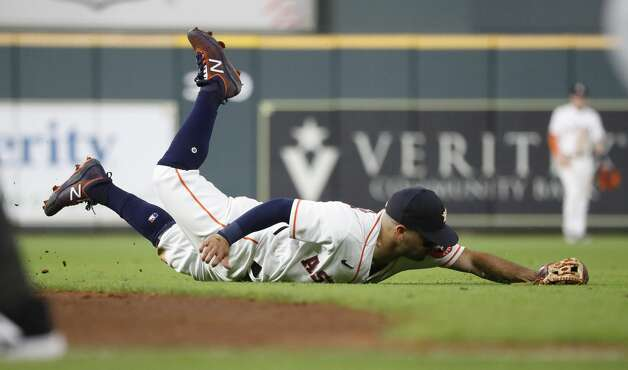 Houston Astros second baseman Jose Altuve (27) dives for a single hit by Seattle Mariners Taylor Trammell during the ninth inning of an MLB baseball game at Minute Maid Park, Monday, April 26, 2021, in Houston. Photo: Karen Warren/Staff Photographer / @2021 Houston Chronicle