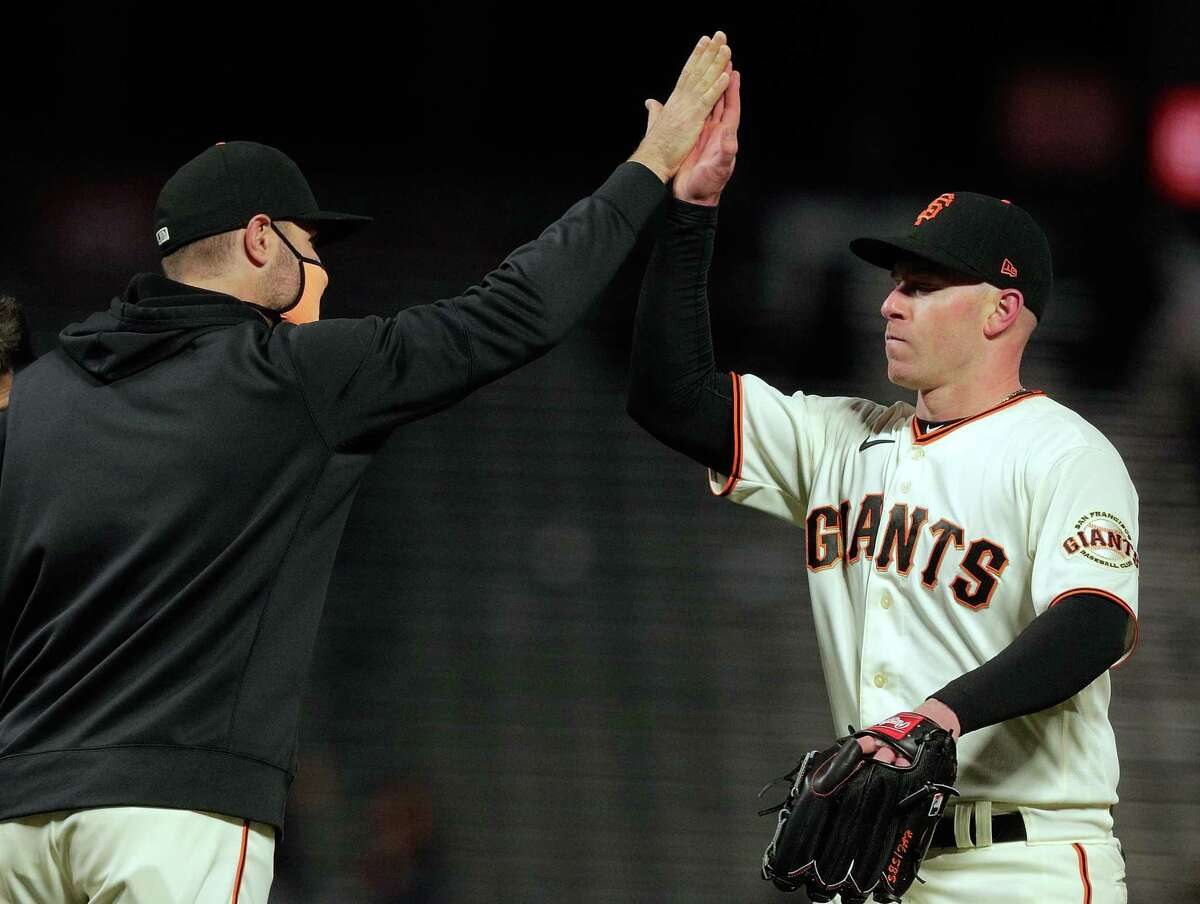 Anthony DeSclafani (26) is congratulated by Giants manager Gabe Kapler after his complete game shutout after the San Francisco Giants defeated the Colorado Rockies 12-0 at Oracle Park in San Francisco Calif., on Monday, April 26, 2021.