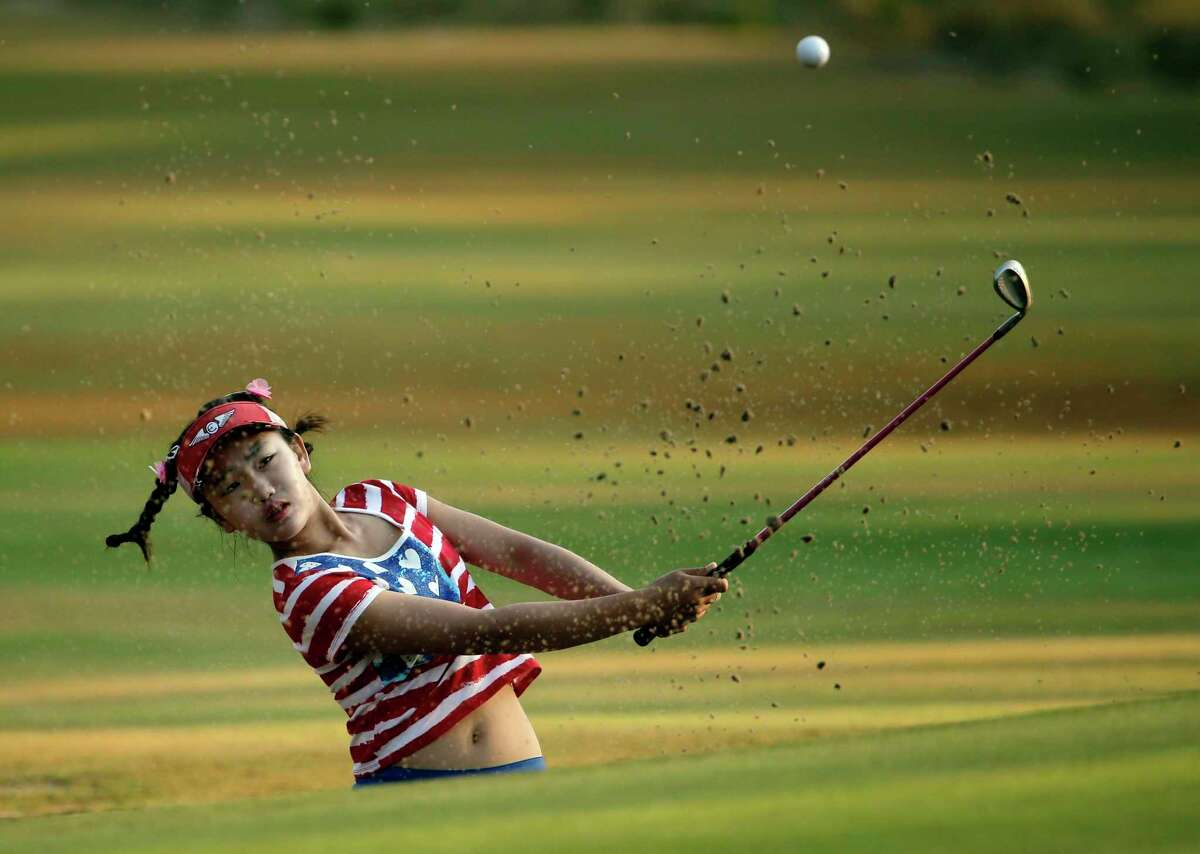 Lucy Li hits from a sand trap on the 10th hole during the first round of the U.S. Women's Open golf tournament in Pinehurst, N.C., Thursday, June 19, 2014. (AP Photo/Chuck Burton)