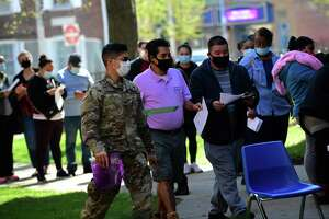 National gurad troops help as local residents line up for the The Griffin Hospital mobile COVID-19 vaccination clinic at the Norwalk Public Library main branch on Belden Ave. Tuesday, April 20, 2021, in Norwalk, Conn. The mobile clinic will be at several locations in Norwalk this week.
