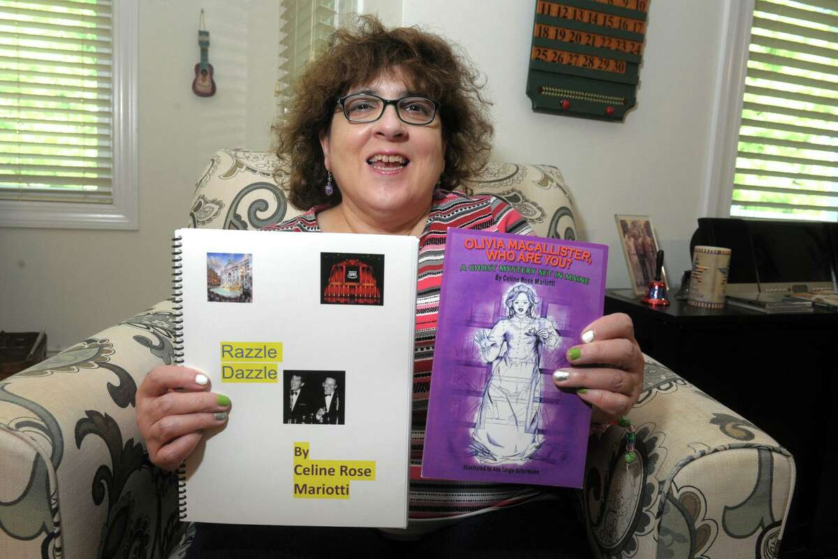 Celine Mariotti poses with a couple of her self-published books in her Shelton, Conn. home April 26, 2021.