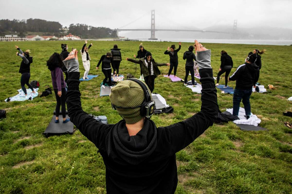 Outdoor Yoga SF instructor Kirin Power leads a class at Crissy Field in San Francisco, with participants distanced. The CDC says vaccinated people can now gather outside without masks.