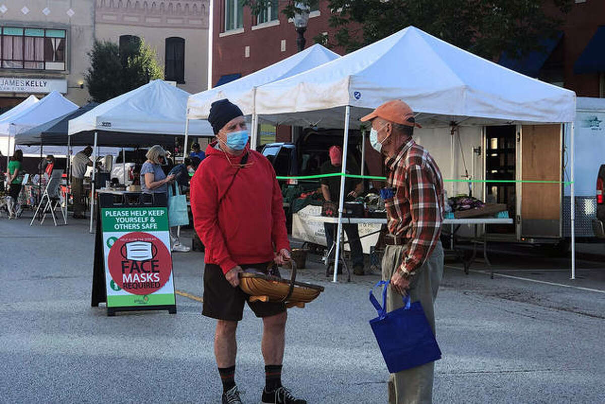 Two friends or neighbors stay socially distanced last year and wear their personal protective equipment during a visit to the Goshen Farmers' Market in 2020.
