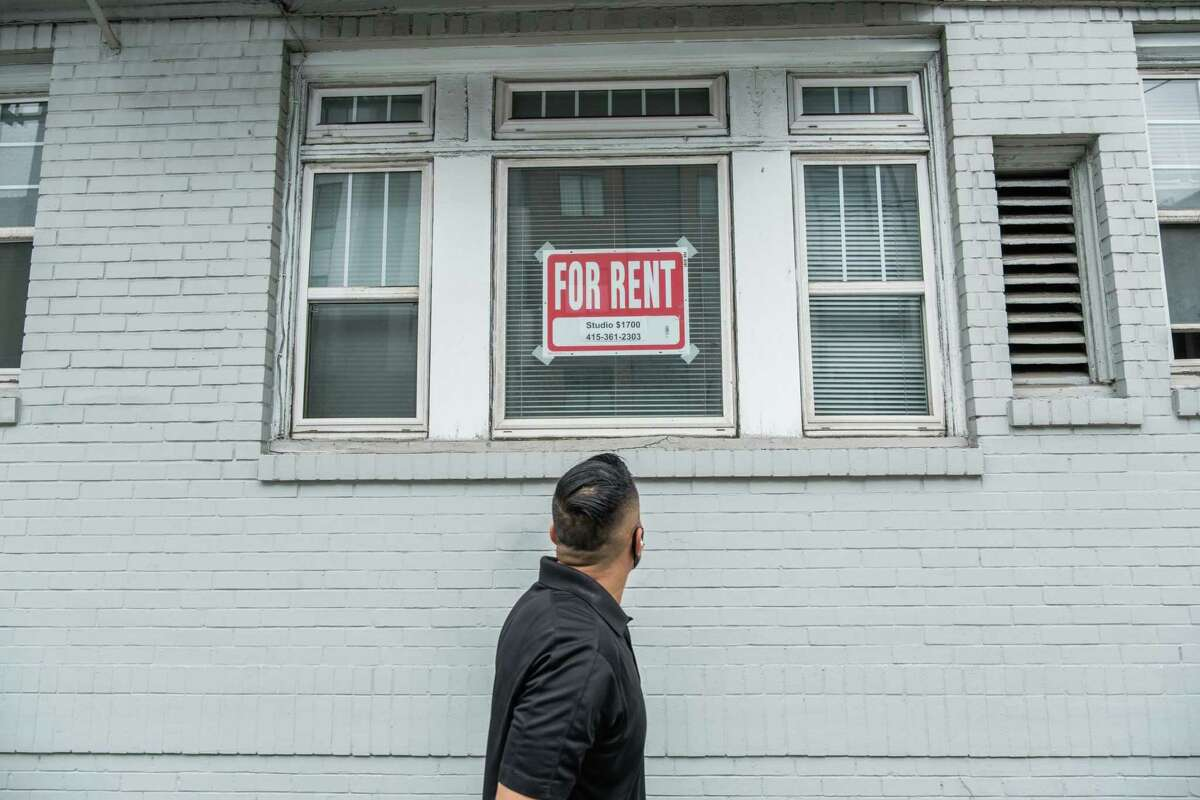 """A pedestrian looks up at a """"For Rent"""" sign in a window on Hayes Street in San Francisco on Friday, October 9, 2020. Rents in San Francisco and throughout the Bay Area continue creeping back up, although they have a long way to go before they catch up to their pre-pandemic highs, new data show."""