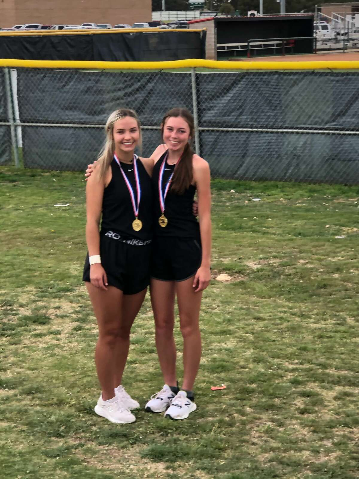 Grady's Raina Short, left, and Samantha Griffin wear their gold medals after winning the girls doubles championship at the Region I-A Tennis Tournament, April 27 in Levelland.