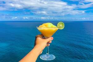 Beautiful woman toasting cocktail in the sea