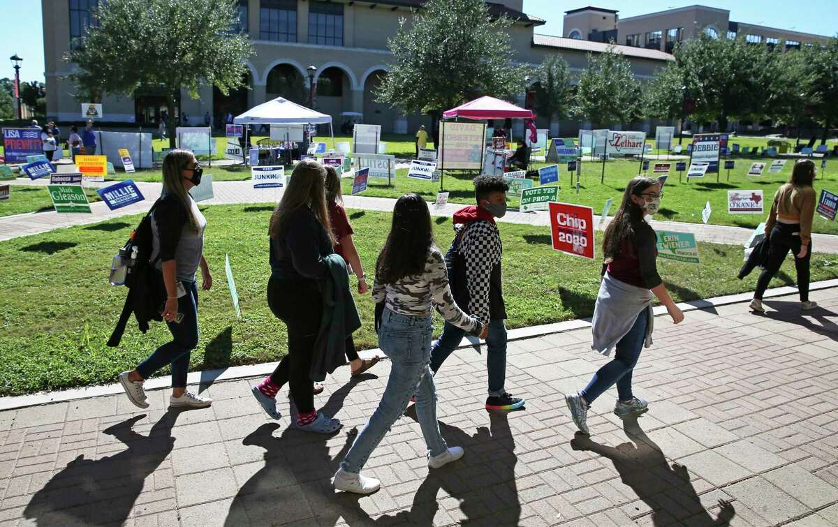 Students at Texas State University walk past campaign signs last fall. Young voters reflect demographic change - and Republicans know this.