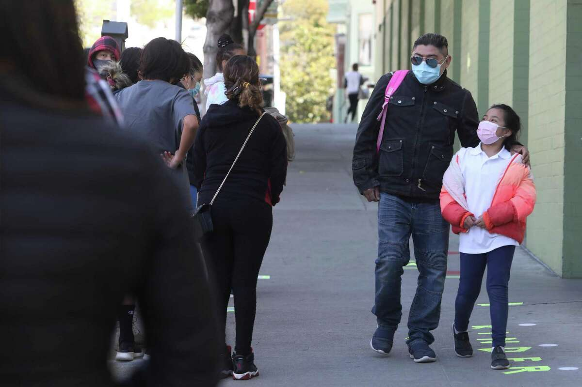 Santiago Jimero (l to r) and his daughter Diana Jimero wear masks as they walk on 25th Street on Tuesday, April 20, 2021 in San Francisco, Calif.