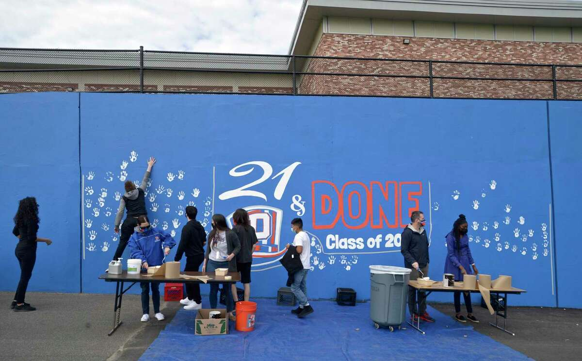 Seniors from Danbury High School leave their hand prints on a mural honoring the Class of 2021on Tuesday morning, April, 27, 2021, in Danbury, Conn.