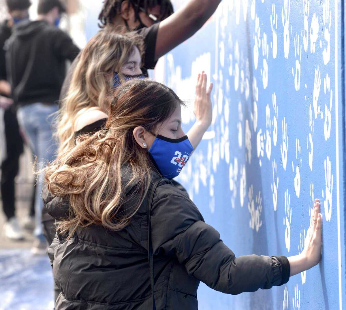 Danbury High School Senior Marlie Penaranda leaves her hand print on a mural honoring the Class of 2021. DHS seniors covered the mural with hand prints on Tuesday morning, April, 27, 2021, in Danbury, Conn.
