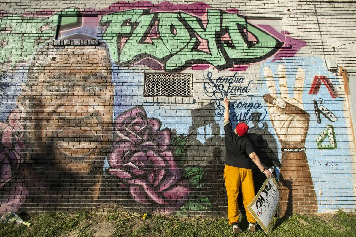 """""""It's a joyous day,"""" Daryel Simmons said as she learned the verdict in the murder trial of former Minneapolis Officer Derek Chauvin in the death of George Floyd on April 20. Simmons reaches up to touch the names of Sandra Bland and Breonna Taylor as she visits a George Floyd mural near the intersection of Ennis and Elgin."""