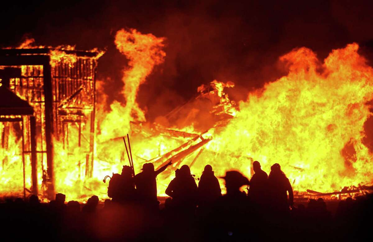 """In this Sept. 3, 2016, file photo, attendees are silhouetted as the structure of the """"Man"""" burns during Burning Man at the Black Rock Desert of Gerlach, Nev., north of Reno. Burning Man organizers announced Tuesday, April 27, 2021, they are canceling this summer's annual counter-culture festival in the Nevada desert for the second year in a row due to the COVID-19 pandemic."""