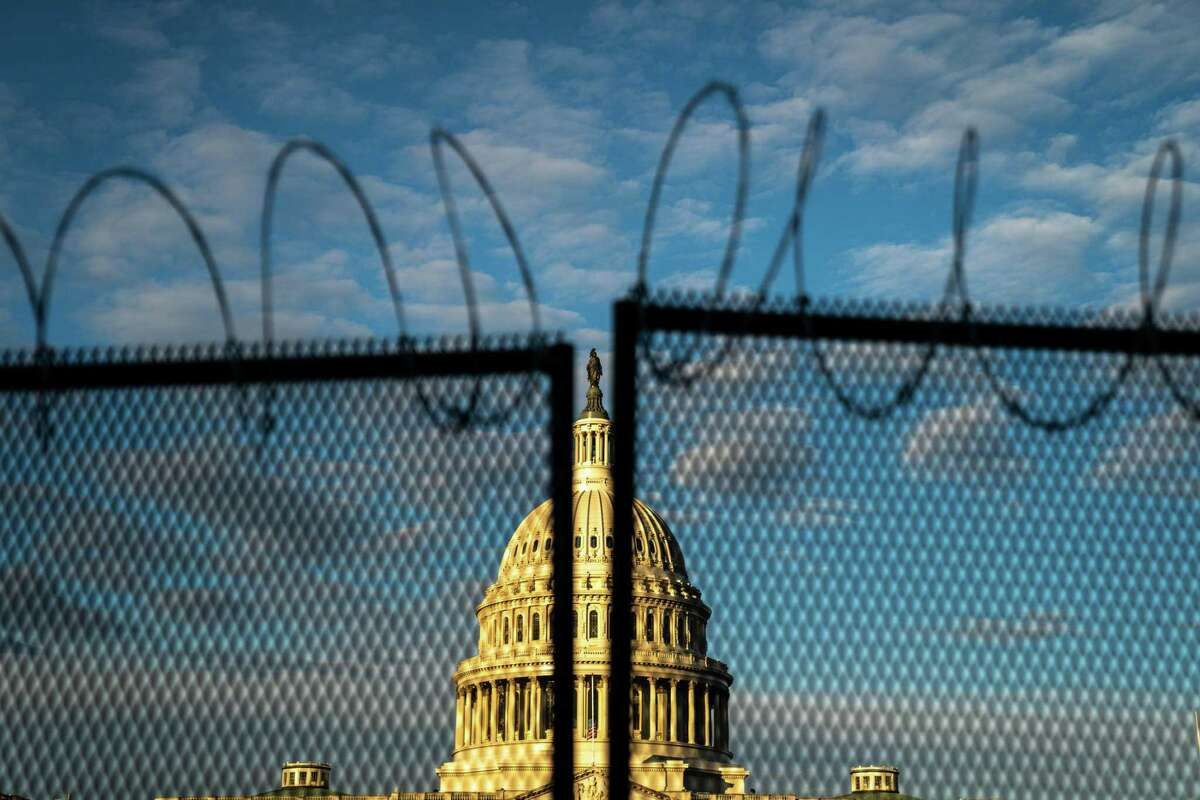 Barbed wire is seen atop security fencing with the dome of the U.S. Capitol Building on Saturday, Jan. 16, 2021, in Washington, D.C. (Kent Nishimura/Los Angeles Times/TNS)
