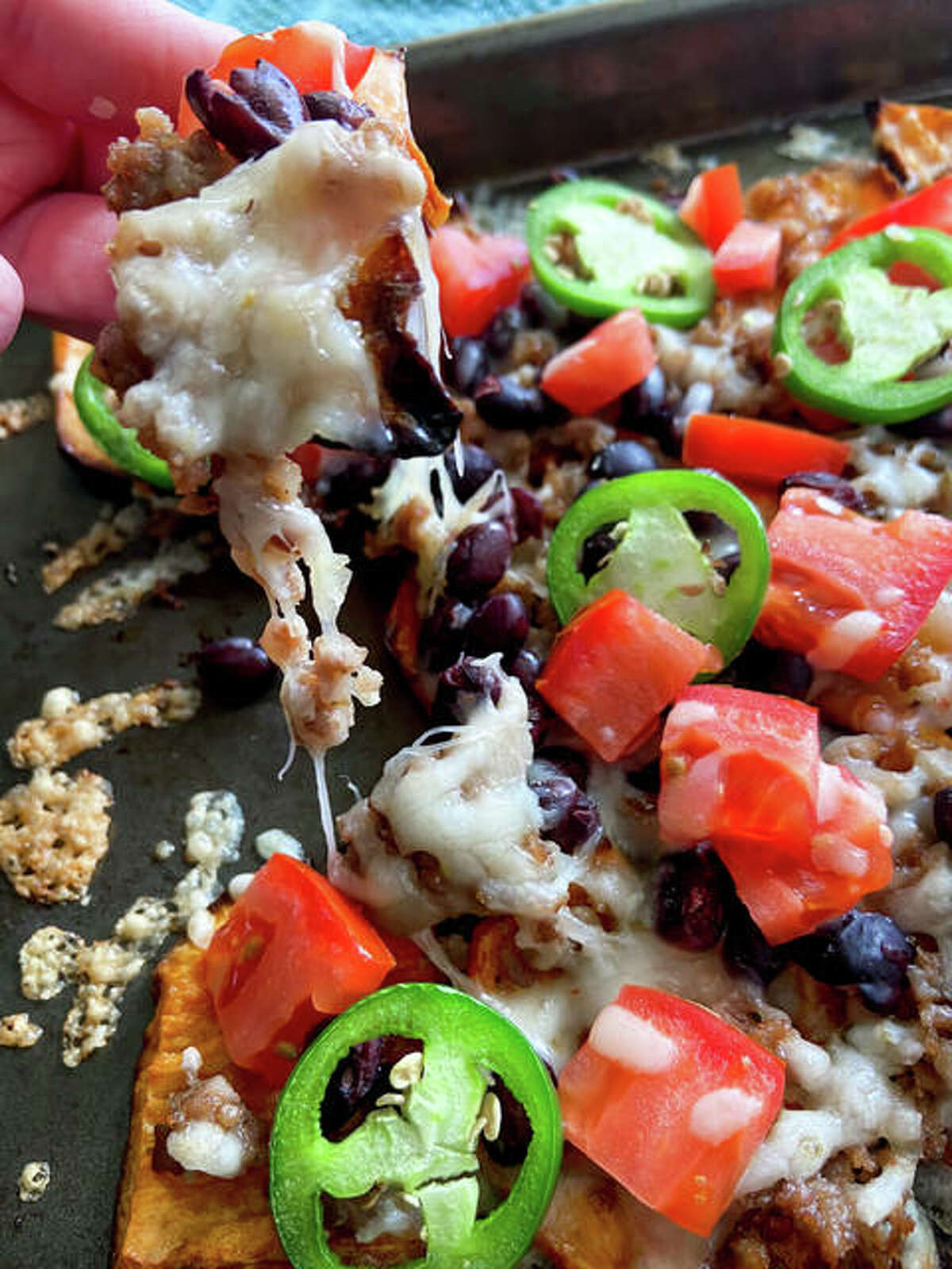 Sweet potato nachos put a healthy twist on the beloved dish, featuring roasted vegetables, black beans, meat, cheese and more.