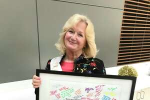 Youth Services Program Assistant Marcia Sacco with a collection of well-wishes for her retirement.