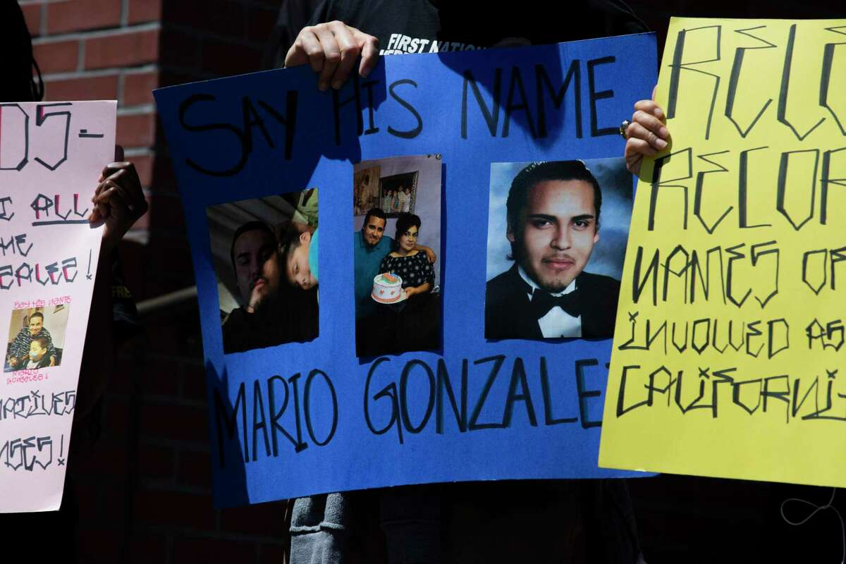 Protesters hold photos of Mario Gonzalez during Tuesday news conference at the Alameda Police Department.