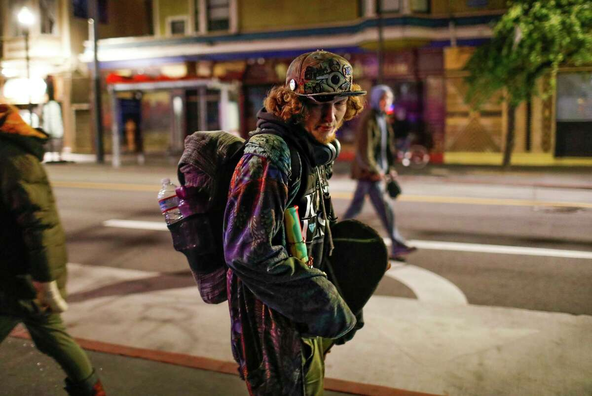 Shadow Haas, 19, who is homeless, makes his way down Haight Street on Monday in San Francisco.