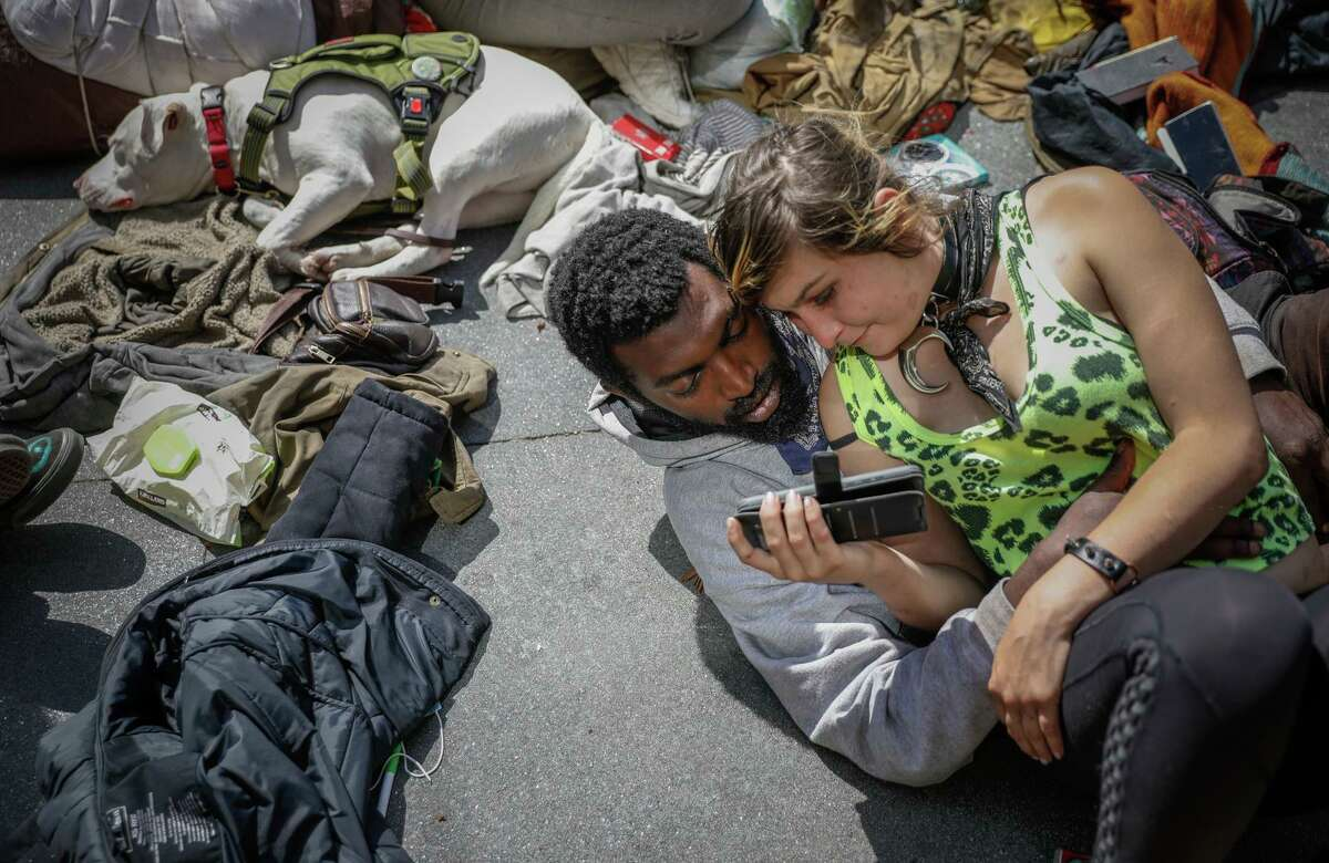 """Chelsea Costello, 22, watches a video with her 26-year-old boyfriend, """"Sharkbait."""" They are homeless and living in the Haight."""