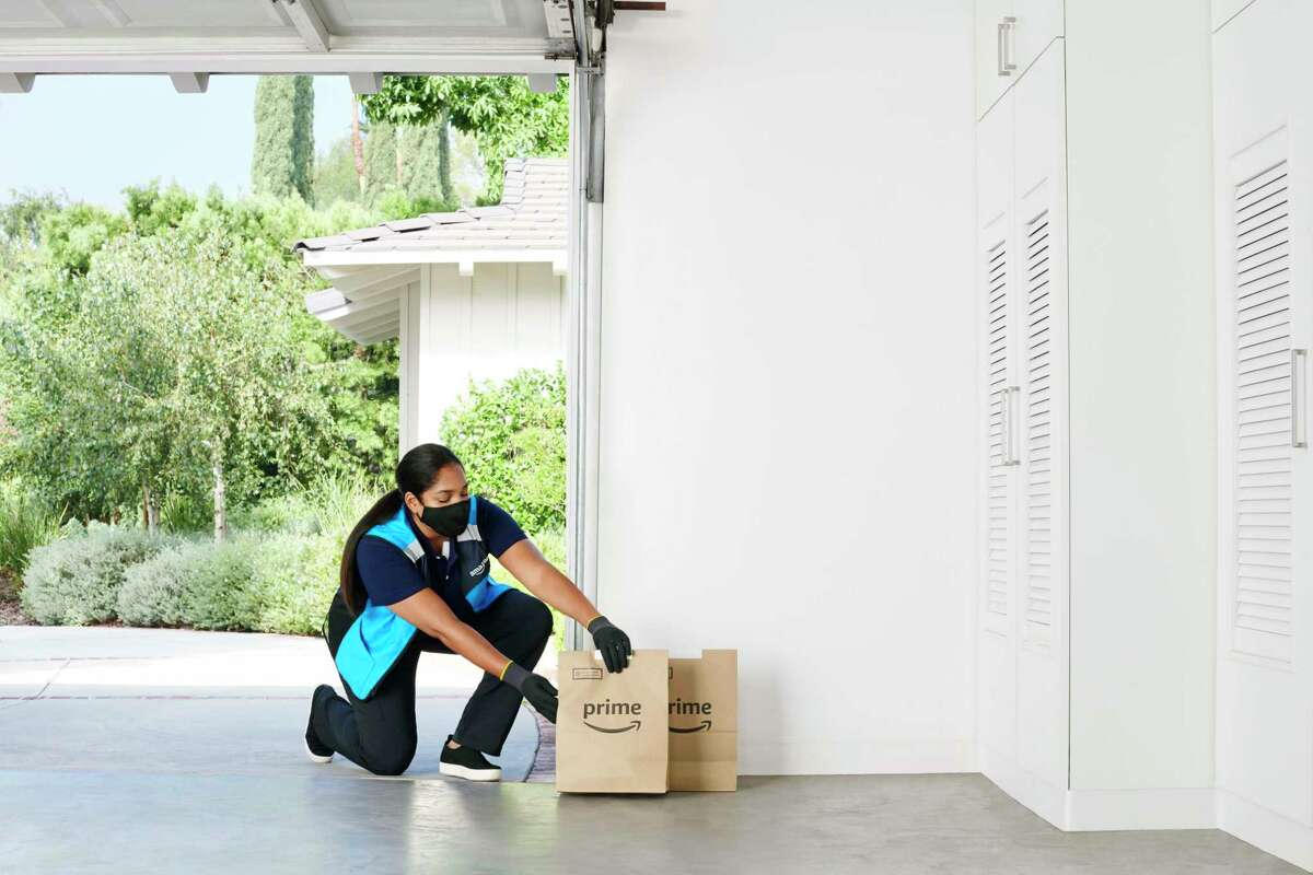 An Amazon delivery person places a grocery order inside a customer's garage. The e-commerce giant has expanded its Key by Amazon In-Garage Grocery Delivery service to more than 5,000 communities nationwide, include select Connecticut sip codes in the Hartford and New Haven areas.