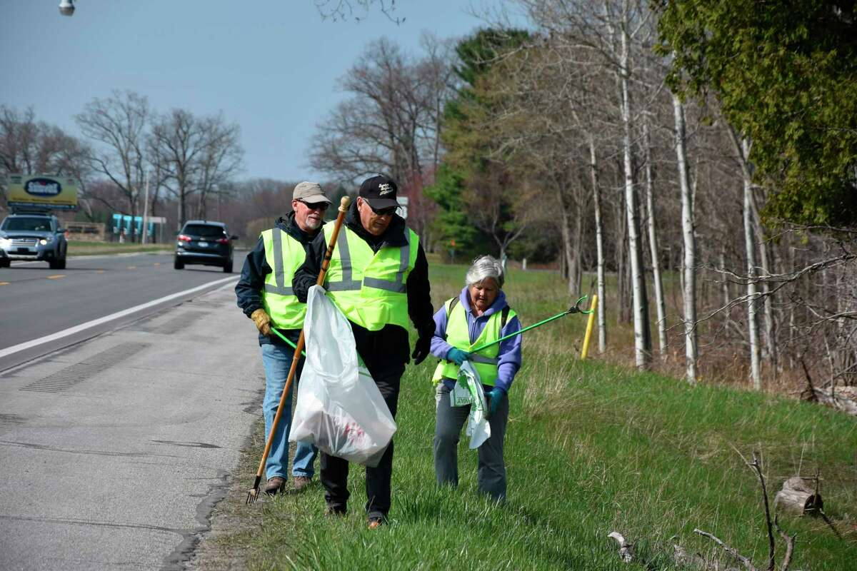 Bill Mason (front), Brett Wakefield and Mary Kay Wakefield scour the grass for trash along U.S. 31 near Manistee County Blacker Airport in Manistee in an effort to clean the area on Friday. (Arielle Breen/News Advocate)
