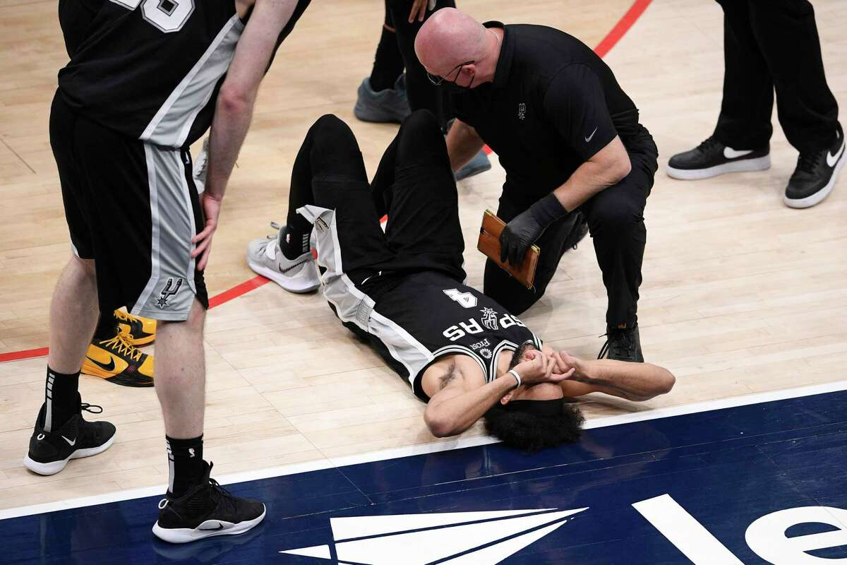 Spurs guard Derrick White (4) lays on the court after he was injured during the second half of an NBA basketball game against the Wizards, Monday, April 26, 2021, in Washington.