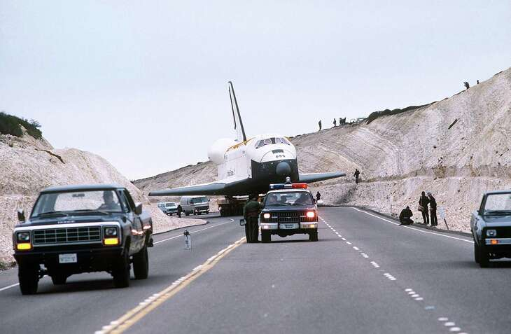 The Space Shuttle Enterprise passes through a hillside that has been cut to clear its wingspan. The orbiter is aboard its specially-designed 76-wheel transporter enroute to Space Launch Complex Six at Vandenberg Air Force Base, Calif.