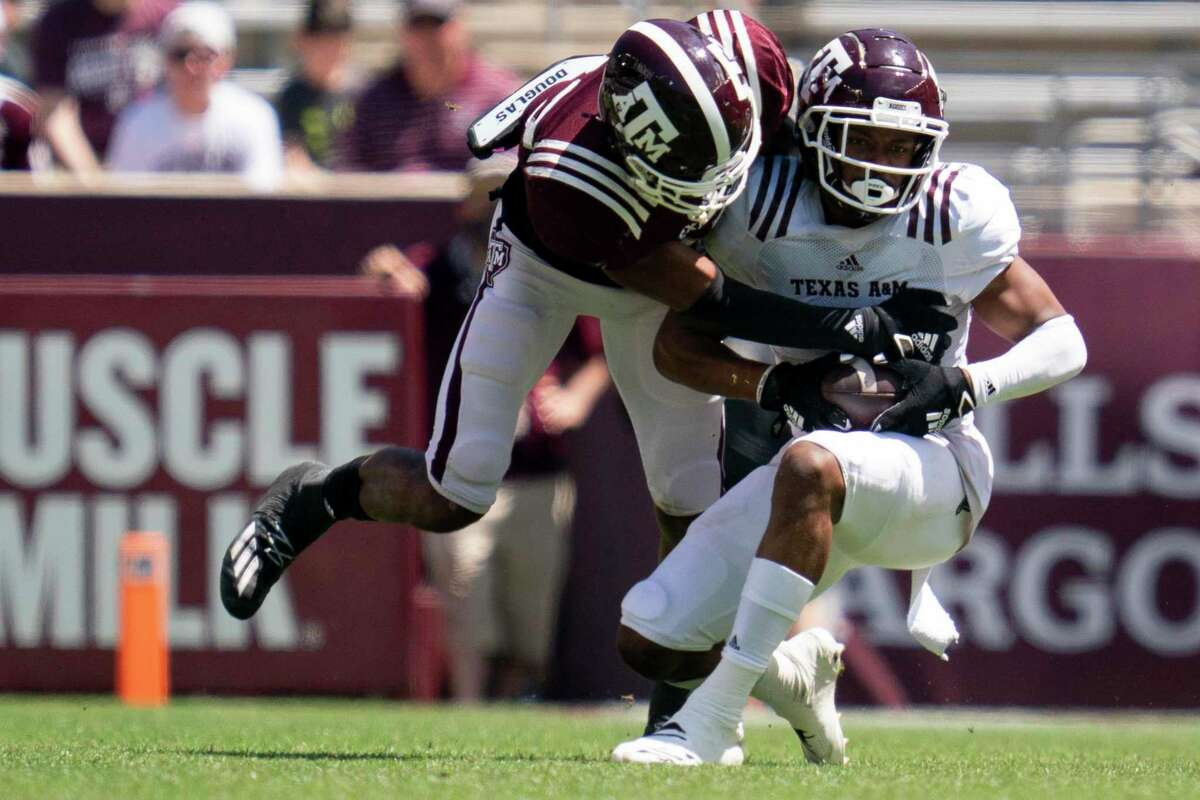 Wide receiver Moose Muhammad III, right, catches a pass against defensive back Antonio Johnson during Texas A&M's Maroon and White spring game in College Station on Saturday.
