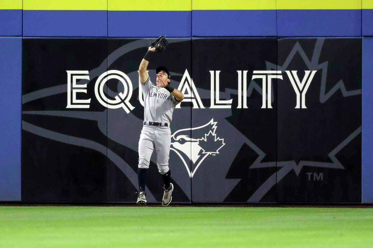 New York Yankees center fielder Mike Tauchman makes a catch on a fly ball from Toronto Blue Jays' Cavan Biggio during the fourth inning of a baseball game Monday, April 12, 2021, in Dunedin, Fla. (AP Photo/Mike Carlson)