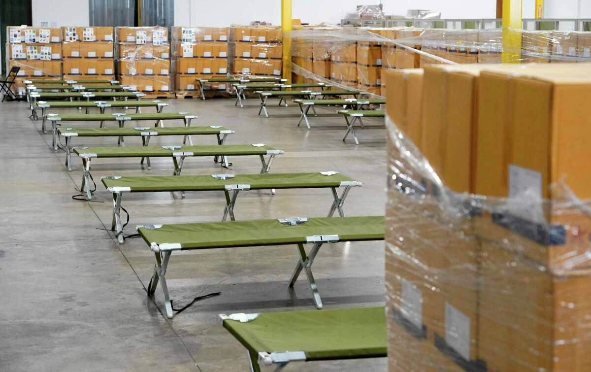 Cots at the National Association of Christian Churches facility that was used as a shelter for unaccompanied immigrant girls ages 13 to 17 are shown Friday, April 23, 2021 in Houston. Pallets of boxes containing plastic cups were used to divided up the areas in the warehouse. After 16 days, all of the girls were transferred.