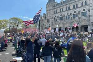 About 4,000 people surrounded the state Capitol Tuesday in a daylong attempt to derail the expected Senate vote that would force new students in all Connecticut schools and child care programs to be vaccinated by September 2022.