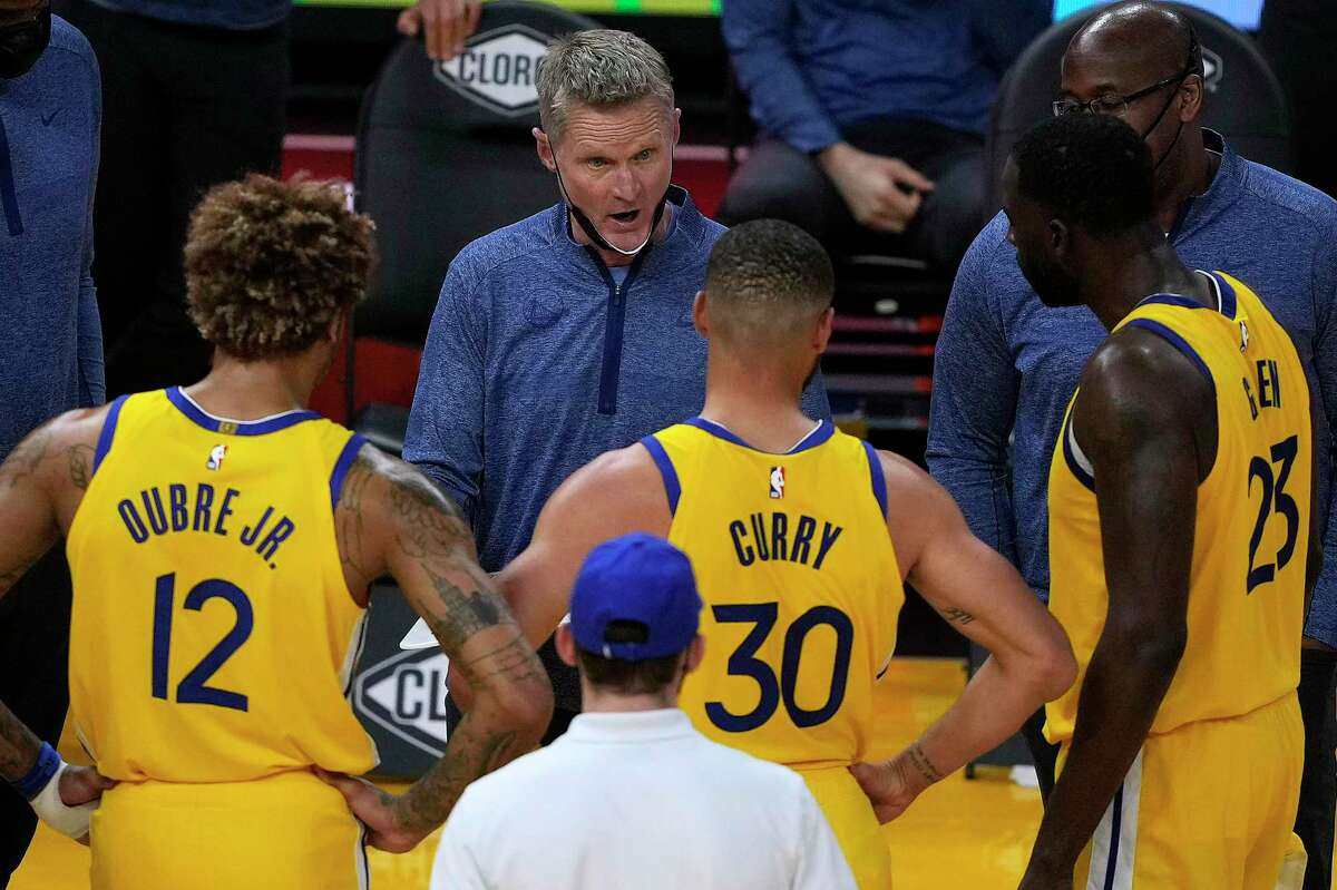 Golden State Warriors coach Steve Kerr, center, talks with his players during a timeout against the Sacramento Kings during the second half of an NBA basketball game on Sunday, April 25, 2021, in San Francisco. (AP Photo/Tony Avelar)