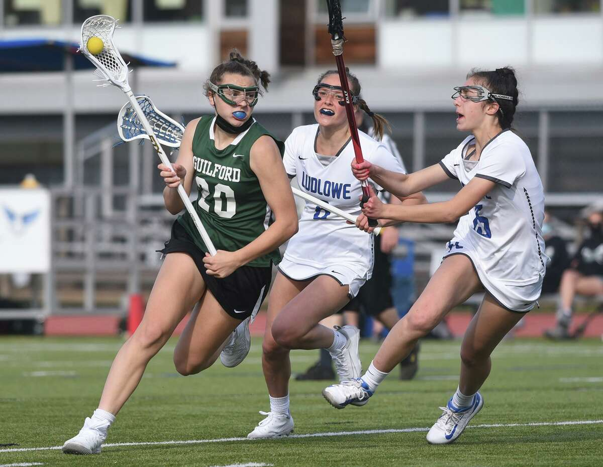 Guilford's Maddie Epke (20) carries the ball while Ludlowe's Quinlyn Shannehan (8) and Sofia Lafalce (15) defend during a girls lacrosse game at Taft Field in Fairfield on Tuesday. April 27, 2021.