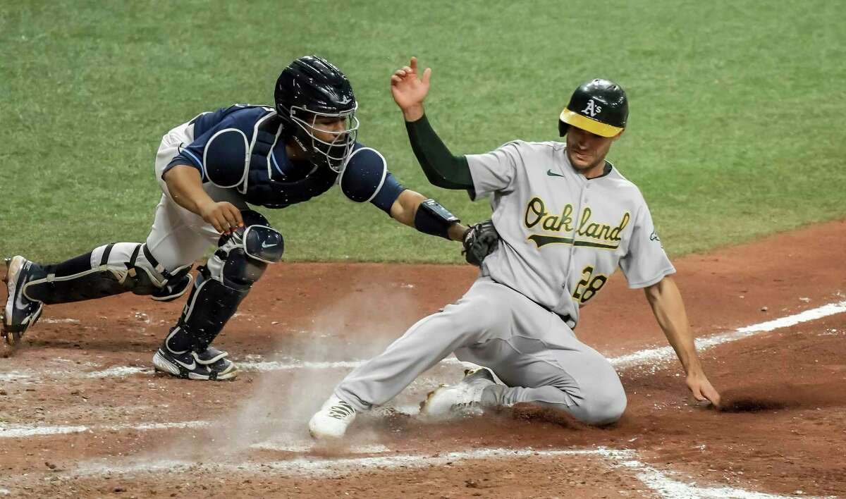 Tampa Bay Rays catcher Francisco Mejia, left, is late with the tag as Oakland Athletics' Matt Olson (28) scores on a sacrifice fly by Mitch Moreland during the sixth inning of a baseball game Tuesday, April 27, 2021, in St. Petersburg, Fla. (AP Photo/Steve Nesius)