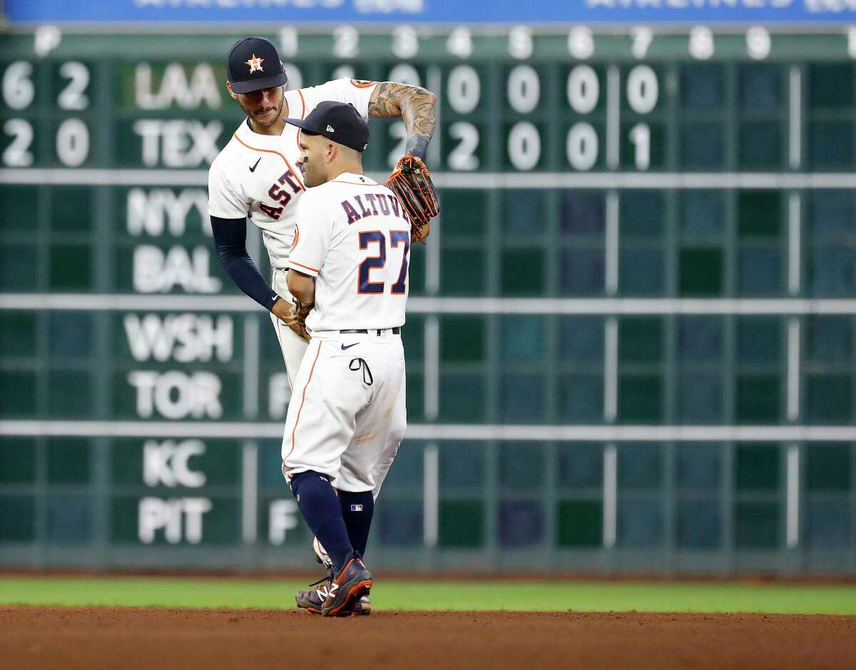 Houston Astros Carlos Correa (1) and Jose Altuve (27) celebrate after the Astros beat the Seattle Mariners 2-0 during an MLB baseball game at Minute Maid Park, Tuesday, April 27, 2021, in Houston.