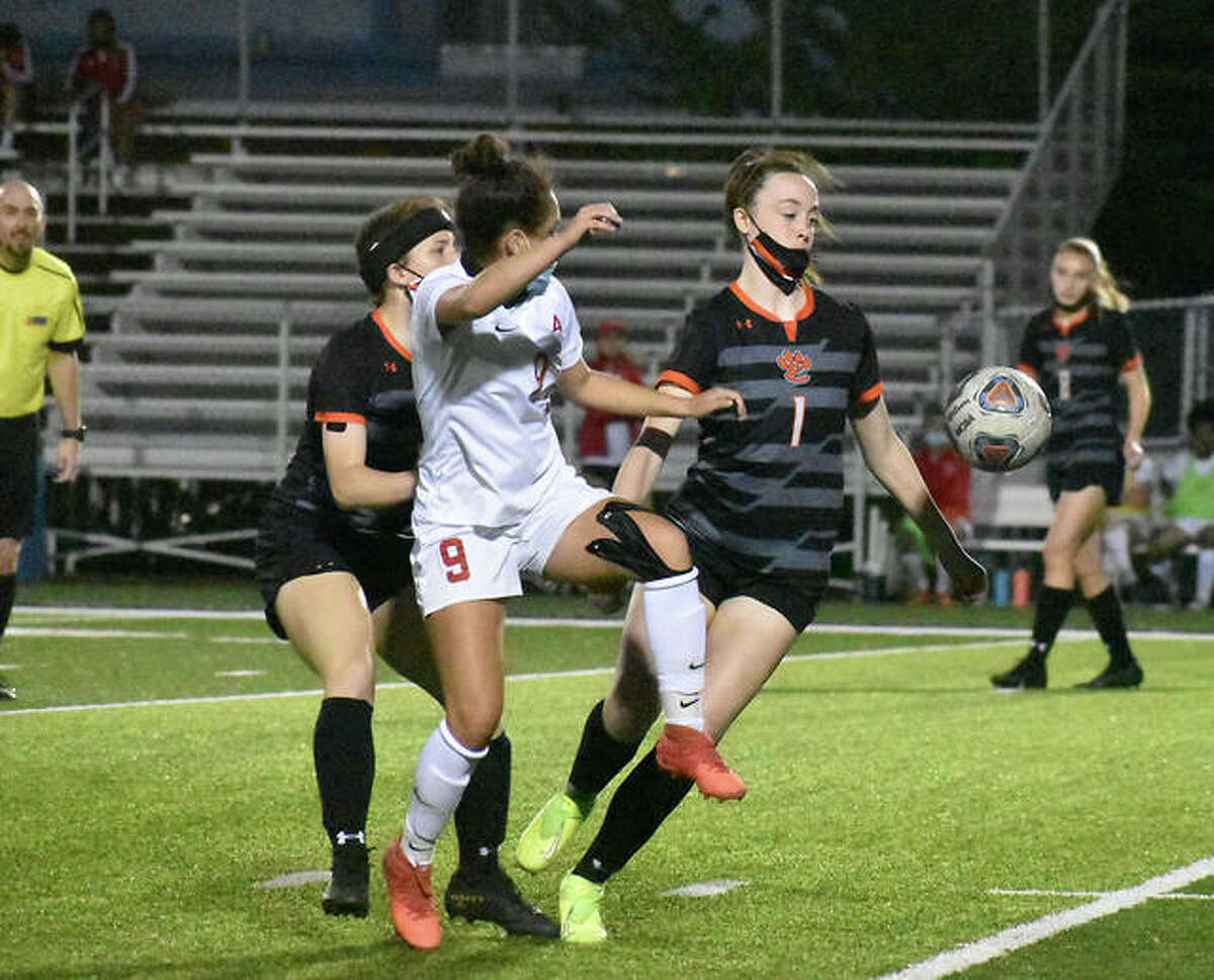 Alton's Emily Baker, center, and Edwardsville's Maya Clark, right, and Amanda Cobb battle for the ball near midfield in the second half on Tuesday in Edwardsville.