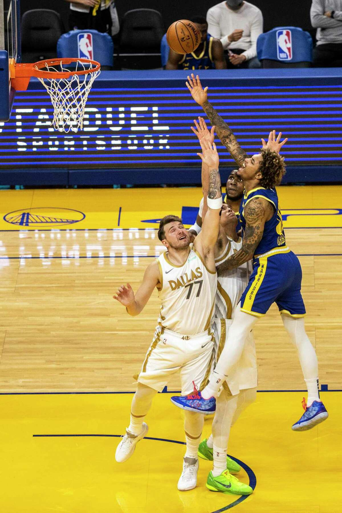 Golden State Warriors guard Kelly Oubre Jr. (12) drives for a layup as Dallas Mavericks guard Luka Doncic (77) defends during the second quarter of their NBA basketball game at Chase Center in San Francisco, Calif. on Tuesday, April 27, 2021.