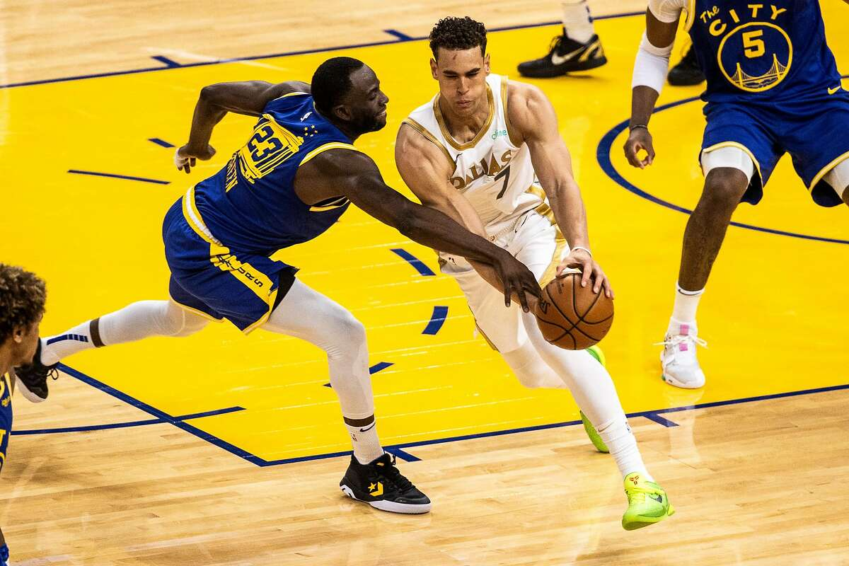 Warriors forward Draymond Green (23) knocks the ball out of the hands of Mavericks center Dwight Powell in the second quarter on Tuesday.