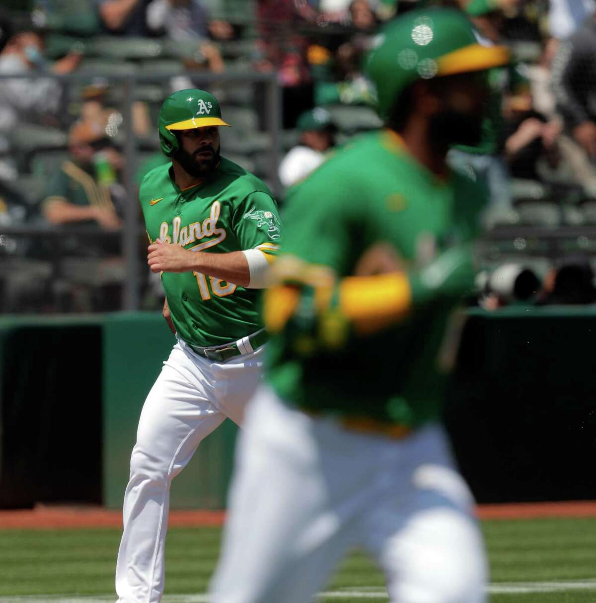 Mitch Moreland (18) scores on a hit by Elvis Andrus (17) in the second inning as the Oakland Athletics played the Minnesota Twins at the Oakland Coliseum in Oakland, Calif., on Wednesday, April 21, 2021.