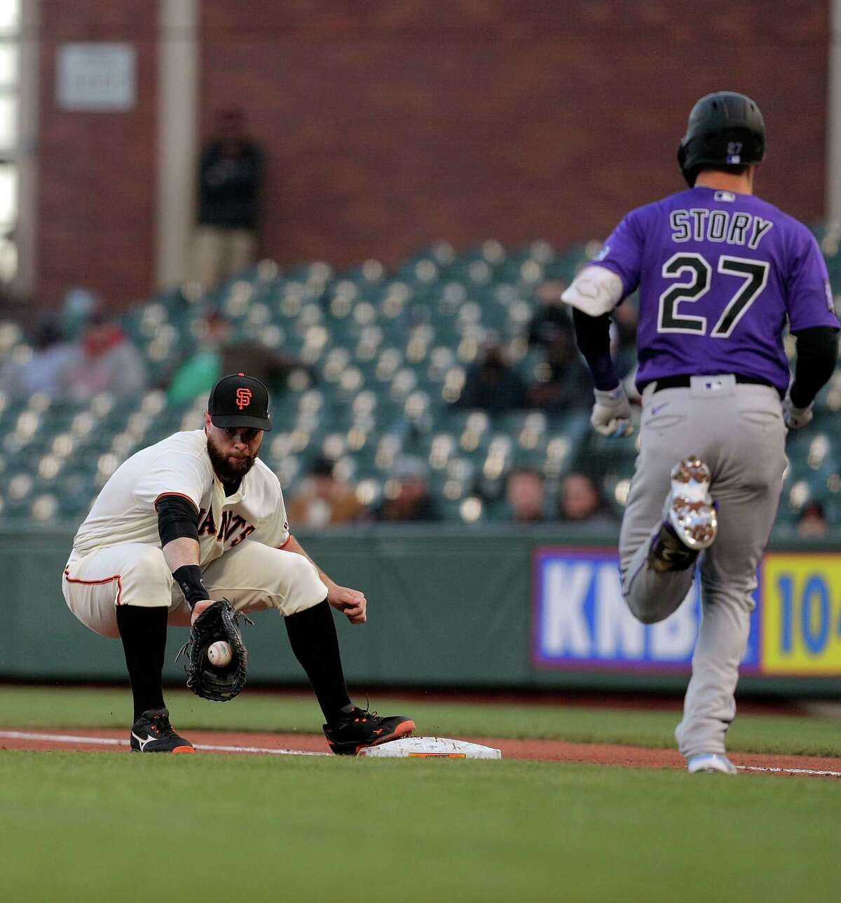 Brandon Belt (9) catches the throw from Aaron Sanchez (21) for the out on a comebacker hit by Trevor Story (27) in the third inning as the San Francisco Giants played the Colorado Rockies at Oracle Park in San Francisco Calif., on Tuesday, April 27, 2021.
